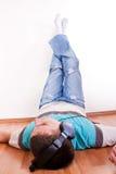El hombre miente en el suelo con los auriculares Imagenes de archivo