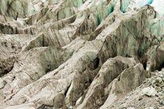 El hombre minúsculo recorre icefield expansivo del glaciar alpestre imágenes de archivo libres de regalías
