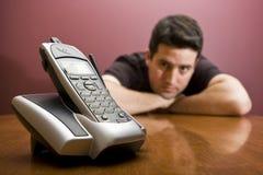 El hombre mira el teléfono. El esperar Imagenes de archivo