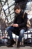 El hombre mira el teléfono en la estación Foto de archivo libre de regalías