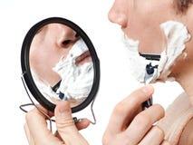El hombre mira en espejo y afeitar fotos de archivo