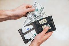 El hombre mira en la cartera efectivo Hombre rico que cuenta su dinero Cierre para arriba imagenes de archivo