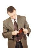 El hombre mira en una cartera vacía Fotografía de archivo libre de regalías