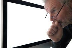 El hombre mira fijamente en la pantalla. Imagen de archivo