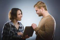 El hombre mira inquiringly el adolescente con el ordenador portátil Concepto del conflicto Fotografía de archivo libre de regalías