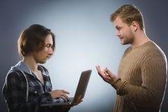 El hombre mira inquiringly el adolescente con el ordenador portátil en fondo gris Fotografía de archivo libre de regalías