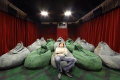 El hombre mira película en pequeño teatro del cine. Imagen de archivo