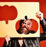 El hombre mira a través de silueta cortada de la calabaza en fondo rojo Concepto del partido de Halloween Demonio con los cuernos Foto de archivo libre de regalías