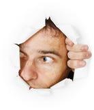 El hombre mira a través del agujero Fotos de archivo
