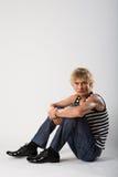 El hombre modelo se sienta en pantalones vaqueros y camisa Fotos de archivo libres de regalías