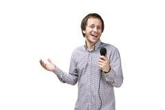 El hombre moderno joven está cantando con el micrófono aislado en los vagos blancos Imagenes de archivo
