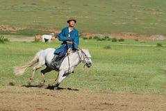 El hombre mongol que lleva el traje tradicional monta en caballo detrás en una estepa en Kharkhorin, Mongolia Imagen de archivo