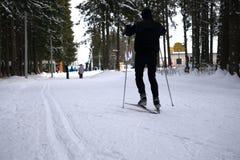 El hombre monta esquí de fondo El ir para arriba la cuesta con el otro siguiente de los esquiadores fotografía de archivo