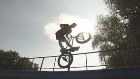 El hombre monta la rueda del onback de la bici de BMX el jinete masculino hace trucos en la bici de BMX almacen de metraje de vídeo