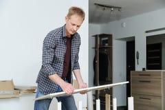 El hombre monta los muebles en casa imagenes de archivo