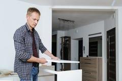 El hombre monta los muebles en casa fotos de archivo libres de regalías