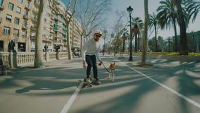El hombre monta su longboard seguido por su perro metrajes