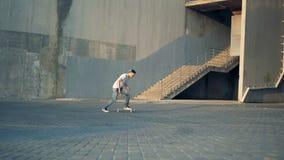 El hombre monta a un tablero y salta en una ciudad mientras que practica almacen de video