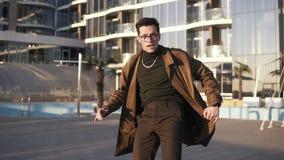El hombre moreno atractivo del younf en vidrios y collar elegantes del oro está realizando danza moderna del estilo libre al aire almacen de metraje de vídeo