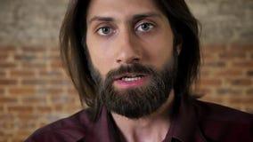 El hombre moreno enojado joven con la barba está mirando en la cámara, gritando, fondo del ladrillo almacen de metraje de vídeo