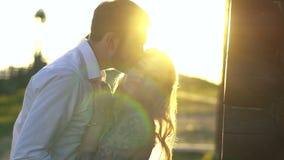 El hombre moreno joven está besando a su amante rubio encantador en la cabeza en el fondo de la puesta del sol Retrato al aire li almacen de video