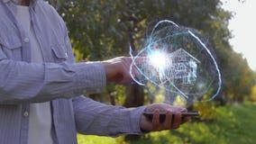 El hombre muestra el holograma con la casa metrajes