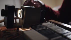 El hombre muestra las fotos en el proyector de diapositiva almacen de metraje de vídeo