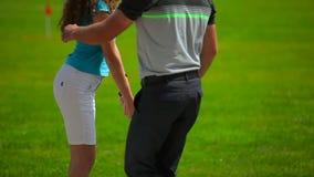 El hombre muestra a muchacha cómo detener a un club en manos en golf metrajes