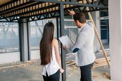 El hombre muestra el plan del trabajo en el cuarto Imagenes de archivo