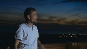 El hombre muestra el pulgar para arriba que disfruta de una opinión de la tarde del tejado metrajes