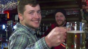 El hombre muestra un vidrio de cerveza en el pub almacen de video