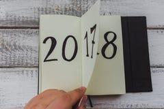 El hombre mueve de un tirón la hoja de la libreta en la tabla de madera blanca 2017 está dando vuelta, 2018 se está abriendo Fotos de archivo