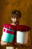El hombre muscular barbudo con el cuerpo atractivo sostiene la caja de la rosa del rojo Imagen de archivo