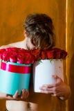 El hombre muscular barbudo con el cuerpo atractivo sostiene la caja de la rosa del rojo Fotografía de archivo libre de regalías