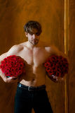 El hombre muscular barbudo con el cuerpo atractivo sostiene la caja de la rosa del rojo Foto de archivo libre de regalías