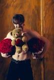 El hombre muscular barbudo con el cuerpo atractivo sostiene la caja de la rosa del rojo Fotos de archivo