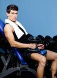 El hombre muscular descansa llevando a cabo un peso en la mano Fotos de archivo