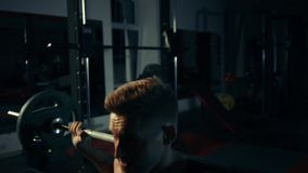 El hombre muscular en el gimnasio que entrena a sus piernas cuadriceps y tendones de la corva con una barra intercambia el concep metrajes