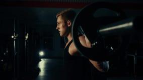 El hombre muscular en el gimnasio que entrena a sus piernas cuadriceps y tendones de la corva con una barra intercambia el concep almacen de video