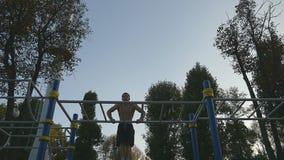 El hombre muscular fuerte que hace el músculo sube en un parque Atleta joven que hace barbilla-UPS en las barras horizontales al  metrajes