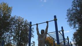 El hombre muscular fuerte que hace el músculo sube en un parque Atleta joven que hace barbilla-UPS en las barras horizontales al  almacen de video