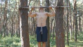 El hombre muscular fuerte que hace tirón sube en un atleta joven del bosque que hace barbilla-UPS en barras horizontales en la ma almacen de video