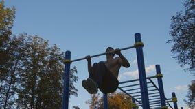 El hombre muscular fuerte que hace tirón sube en un parque El atleta joven que hace barbilla-UPS y realiza ejercicios en barras h almacen de video