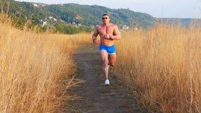 El hombre muscular hace el ejercicio cardiio que corre al aire libre