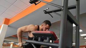 El hombre muscular joven durante el entrenamiento en el gimnasio realiza flexiones de brazos en las barras almacen de metraje de vídeo