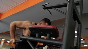 El hombre muscular joven durante el entrenamiento en el gimnasio realiza flexiones de brazos en las barras almacen de video