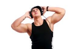 El hombre muscular joven escucha música Fotos de archivo libres de regalías