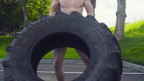 El hombre muscular joven que hace el crossfit ejercita al aire libre metrajes