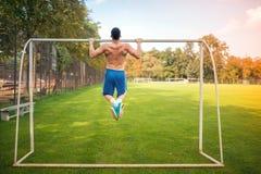 El hombre muscular joven que hace tirón sube en la corte del fútbol, entrenamiento incondicional al aire libre fotos de archivo