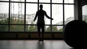 El hombre muscular que hace salto de la cuerda se resuelve en el gimnasio - silueta, a cámara lenta almacen de metraje de vídeo